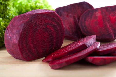 beets: Close up of fresh beet cut into slices with green salad