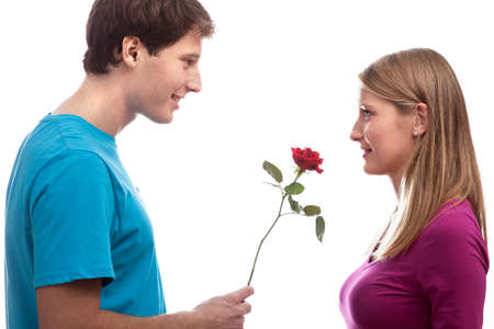 Young man giving a red rose to his girlfriend photo