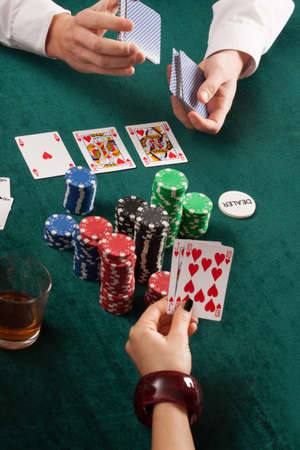 croupier: Cards, colorful poker chips and alcohol in casino Stock Photo