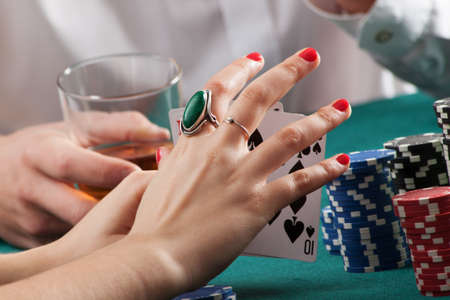 gambling chip: Woman hands on green casino table holding playing cards