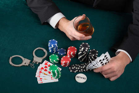 Gambler holding a glass of alcohol and handcuffs photo