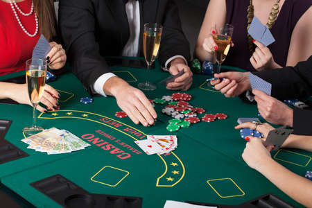 poker chips: People sitting at casino table playing cards and drinking champagne