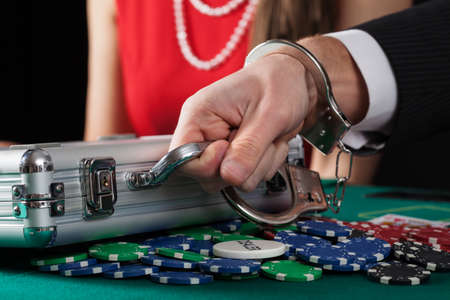 Suitcase with money on casino table handcuffed to man photo