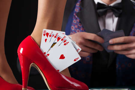 Royal flush in womans red high heels Stock Photo