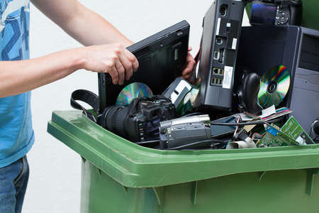 Putting used and old computer hardware into the dustbin. Banco de Imagens - 24229487