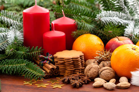 Candles, fruits, cookies and nuts among the spruce twigs photo