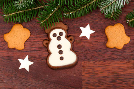 Gingerbread snowman on wooden background and spruce twig photo