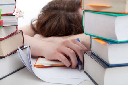 stress test: Exhausted student lying on a desk behind a books