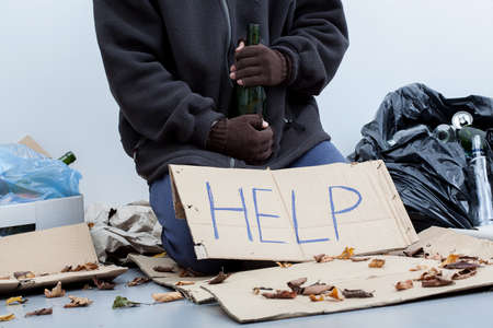 Homeless alcoholic sitting around the trash bags and holding an empty bottle Stock Photo - 24368882