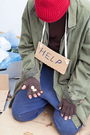 Homeless person in need holding only a few cents in his hand Stock Photo