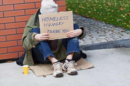 Jonge arme bedelaar zit op een karton en vragen om hulp Stockfoto