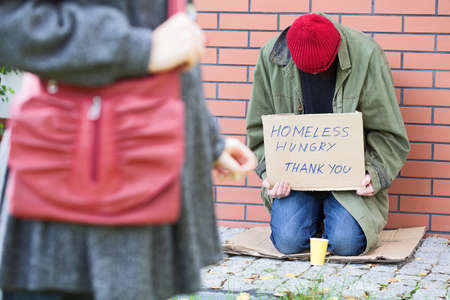 street corner: Woman passing poor homeless and hungry man Stock Photo