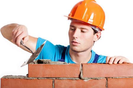 brick work: Construction mason installing red brick with trowel