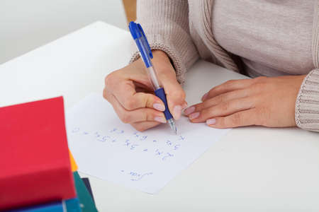 article writing: Student writing the math problems on the piece of paper  Stock Photo