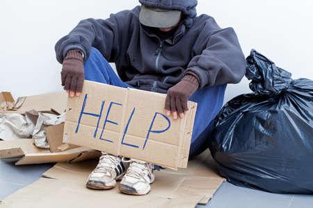 limosna: Persona sin hogar sentado en el suelo y pidiendo ayuda