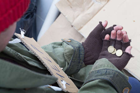 Hands of homeless person holding a few cents photo