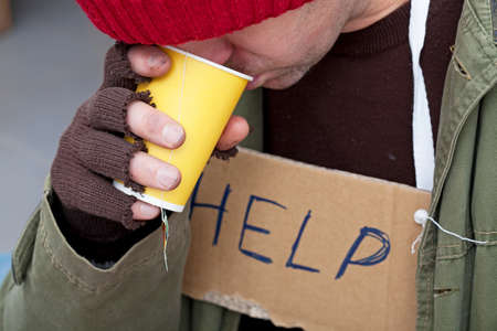 poor people: Homeless with cardboard on his neck drinkig hot tea Stock Photo