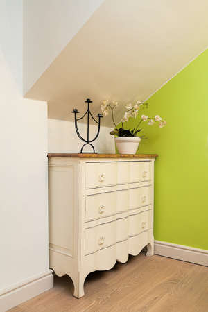 chest of drawers: Vintage mansion - a cream chest of drawers with a flower and a candleholder