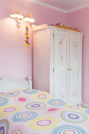 Vintage mansion - a girly bedroom with a colorful bed and a white wardrobe photo