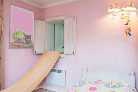 Vintage mansion - apink wall of a girl's bedroom with a slide, a lamp and a painting photo