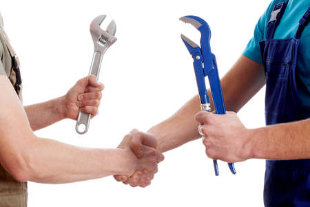 Two manual workers with tools shaking their hands photo