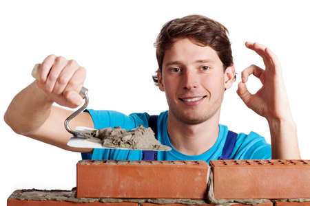 brick mason: Happy man with putty knife building a brick wall Stock Photo