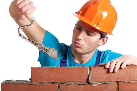 Constructor with putty knife building a brick wall photo