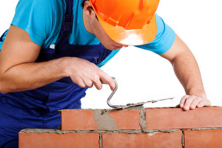 Handyman with trowel installing red brick photo