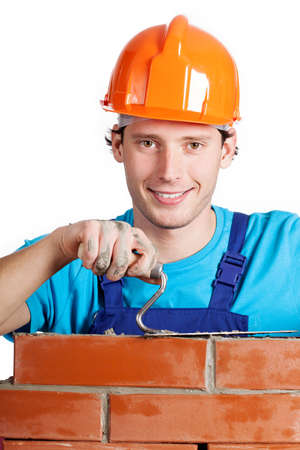 Happy handyman in hardhat with trowel and brick photo