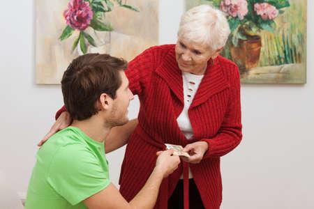 внук: Бабушка дает деньги на карманные расходы для внука Фото со стока