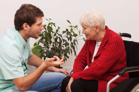 lonely person: Nurse keeping company to disabled elderly lonley person Stock Photo