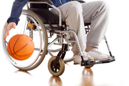 A disabled basketball player in a tracksuit with a ball Stock Photo