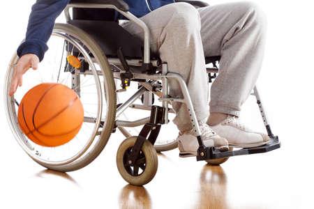persona en silla de ruedas: Un jugador de baloncesto con discapacidad en un ch�ndal con una pelota Foto de archivo