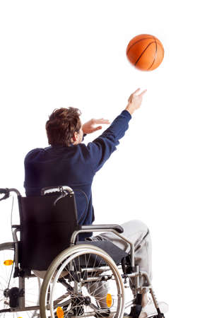 A disabled man on a wheelchair throwing a basketball photo