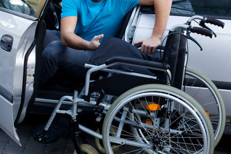 consist: Handicapped driver sitting already in his car and consisting his wheelchair Stock Photo