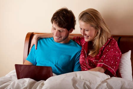 Couple watching together the movie in bed before going to sleep photo
