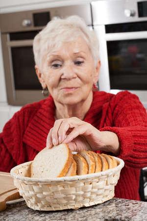 高齢者は自分の朝食を準備する女性を無効に