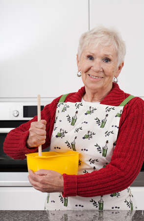 Happy active grandma is baking cookies at home photo
