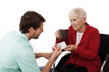 Nurse giving medicines to elder disabled person on wheelchair