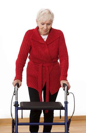 Oudere gehandicapte vrouw loopt met rollator Stockfoto