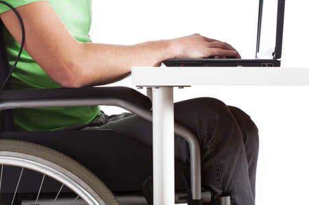 Disabled man sitting on wheelchair at a desk photo