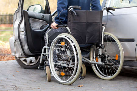 disability insurance: A disabled driver using a wheelchair entering his car