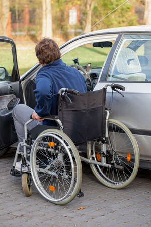 disability insurance: Independent man on a wheelchair next his car Stock Photo