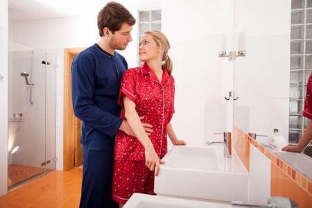 bathroom women: Couple in pajamas in the bathroom before going to sleep Stock Photo