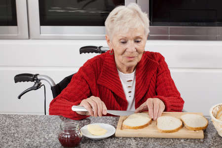 assisted living: Disabled older woman preparing sandwiches for breakfast Stock Photo