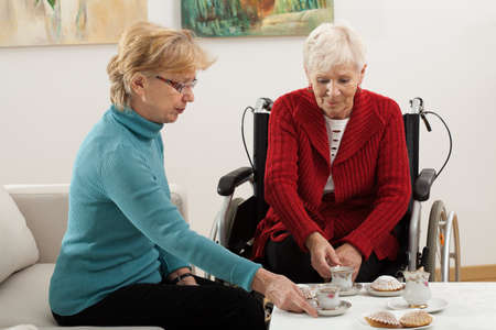 Two elder women drinking coffee and spending time together photo