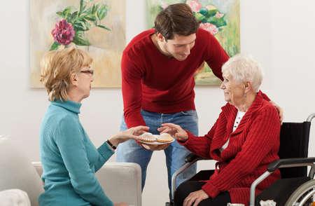 amigas conversando: Familia haciendo compañía al anciano discapacitado