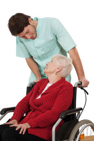 Nurse keeping company to elder disabled woman on wheelchair photo
