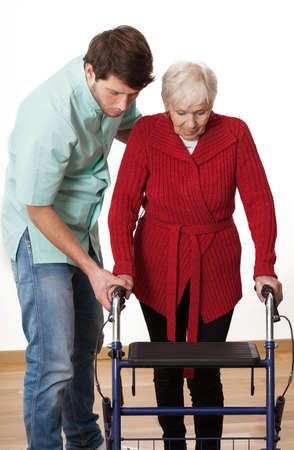 assisted living: Nurse teaching elder disabled person how to walk with walker  Stock Photo