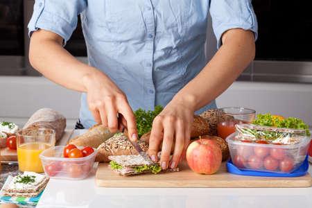 bocadillo: Una persona que corte un s�ndwich mientras que hace un almuerzo saludable Foto de archivo